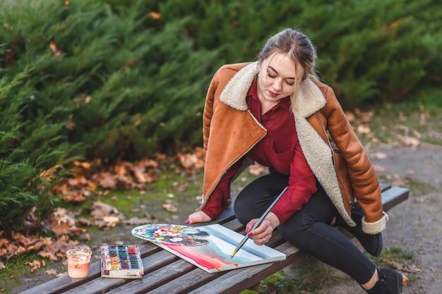Młody malarz rysuje zdjęcie siedzącego w parku na ławce
