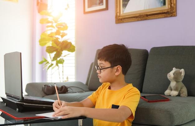 Młody mały chłopiec w okularach, siedząc w pobliżu kanapy w salonie w domu i odrabiaj lekcje podczas nauki klasowej za pomocą laptopa.