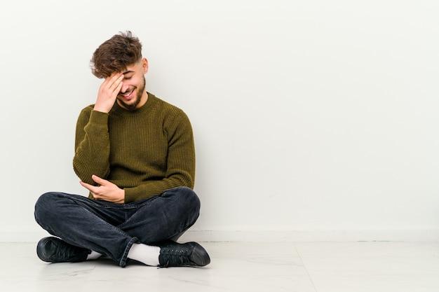 Młody marokańczyk siedzący na podłodze na białej ścianie mruga przez palce, zawstydzony zakrywający twarz.