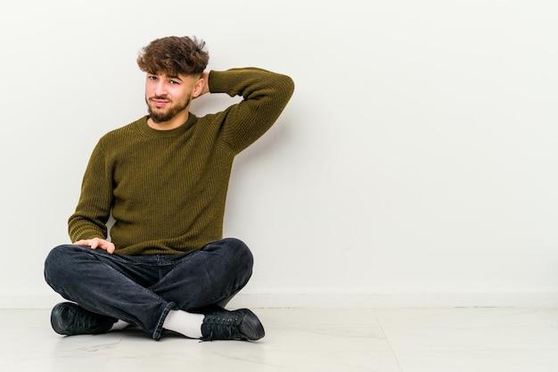 Młody marokańczyk siedzący na podłodze na białym tle cierpi na ból szyi z powodu siedzącego trybu życia.