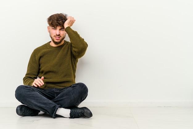 Młody marokańczyk siedzący na podłodze zapominając o czymś, klepie dłonią w czoło i zamyka oczy.