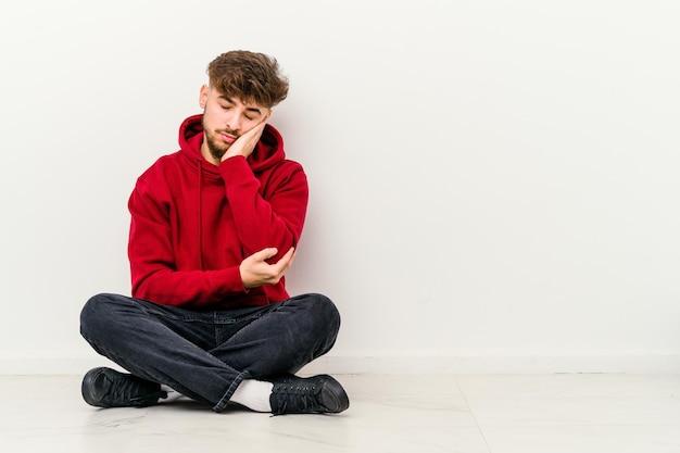 Młody marokańczyk siedzi na podłodze na białym tle, który jest znudzony, zmęczony i potrzebuje dnia relaksu.