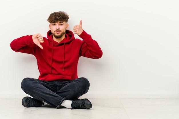 Młody marokańczyk siedzi na podłodze na białym tle na białej ścianie, pokazując kciuki w górę i w dół, trudna koncepcja wyboru