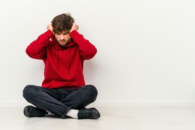 Młody marokańczyk siedzi na podłodze na białym tle na białym obejmujące uszy rękami, starając się nie słyszeć zbyt głośnego dźwięku.