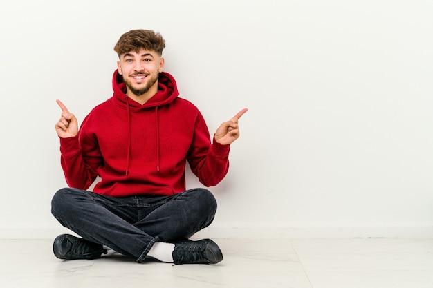 Młody marokańczyk siedzi na podłodze na białym tle, wskazując na różne miejsca kopiowania, wybierając jedną z nich, pokazując palcem.