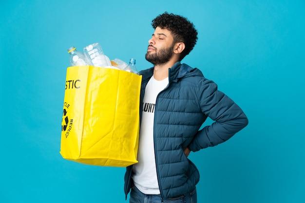 Młody marokańczyk trzymający torbę pełną plastikowych butelek do recyklingu na odosobnionym tle cierpiący na bóle pleców z powodu wysiłku