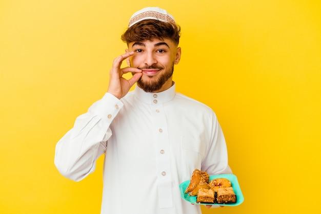 Młody marokańczyk ubrany w typowy strój arabski, jedzący arabskie słodycze na białym tle na żółtym tle z palcami na ustach, zachowując tajemnicę.