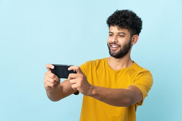 Młody marokański mężczyzna na białym tle na niebieskiej ścianie, grając z telefonem komórkowym