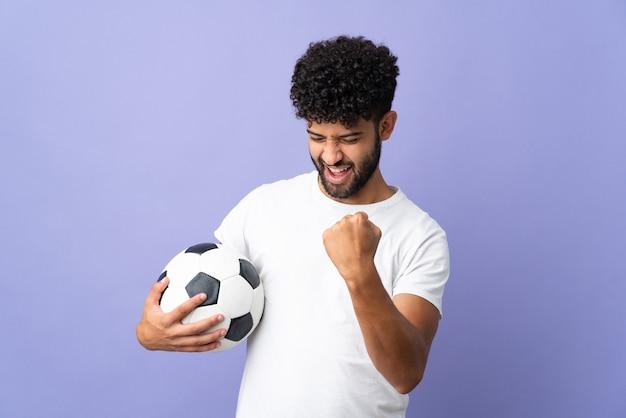 Młody marokański mężczyzna na fioletowym tle z piłką nożną świętującą zwycięstwo