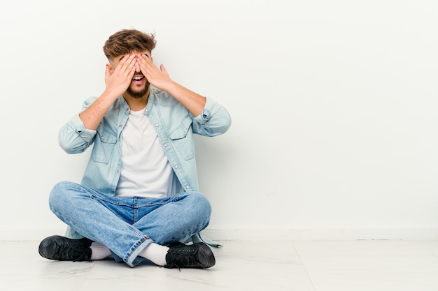 Młody marokański mężczyzna siedzi na podłodze, boi się, zakrywając oczy rękami.