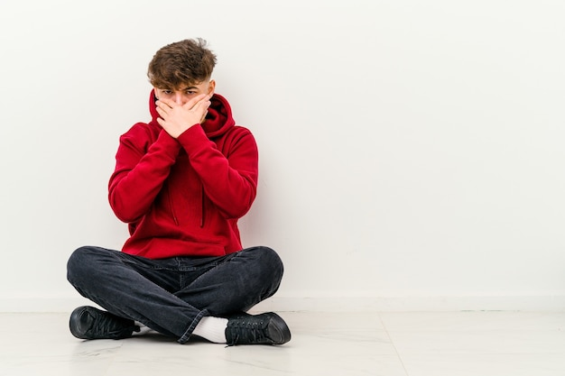 Młody marokański mężczyzna siedzi na podłodze na białym tle na białej ścianie zakrywającej usta rękami wyglądającymi na zmartwionego.