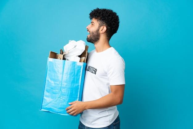 Młody marokański mężczyzna trzyma worek recyklingu pełen papieru do recyklingu na białym tle śmiejąc się w pozycji bocznej