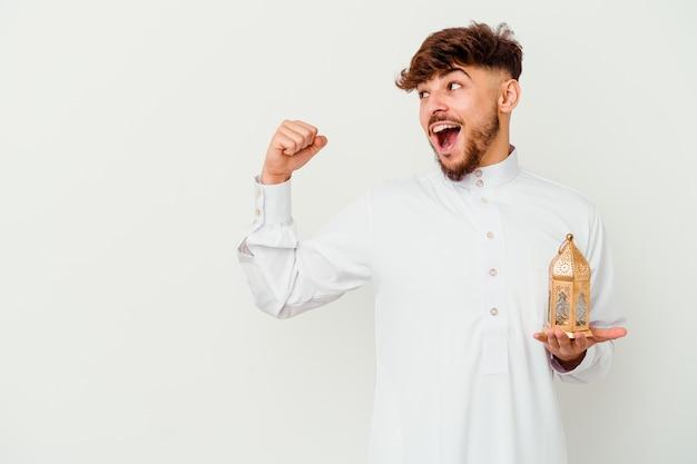 Młody marokański mężczyzna ubrany w typowe arabskie stroje trzymając lampę ramadan na białym, podnosząc pięść po zwycięstwie, koncepcja zwycięzcy.