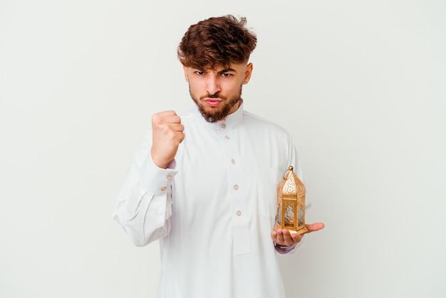 Młody marokański mężczyzna ubrany w typowe arabskie stroje trzymając lampę ramadan na białym tle pokazując pięść do kamery, agresywny wyraz twarzy.
