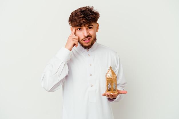 Młody marokański mężczyzna ubrany w typowe arabskie stroje trzymając lampę ramadan na białym tle pokazujący gest rozczarowania palcem wskazującym.