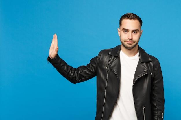 Młody martwi się nieogolony mężczyzna w czarnej kurtce biały t-shirt pokazując gest stop z palmą na białym tle na tle niebieskiej ściany portret studio. koncepcja życia szczere emocje ludzi. makieta miejsca na kopię.