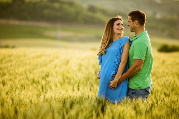 Młody mąż i jego ciężarna żona w polu lato