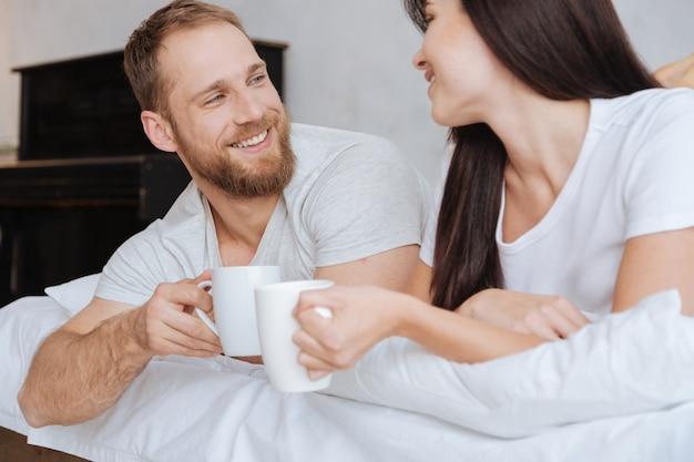 Młody mąż i żona leżą w łóżku przy filiżance kawy i rano rozmawiają na poduszki