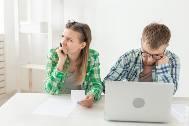 Młody mąż i żona są zdenerwowani licznymi czekami na płatności i zakupami na naprawy
