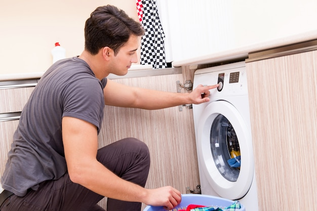 Młody mąż mężczyzna robi pranie w domu