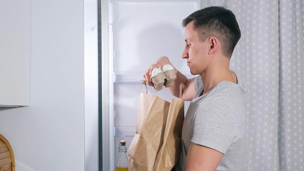 Młody mąż w koszulce wkłada różne świeże produkty spożywcze z papierowej torby do dużej lodówki we współczesnej, lekkiej kuchni, widok z boku