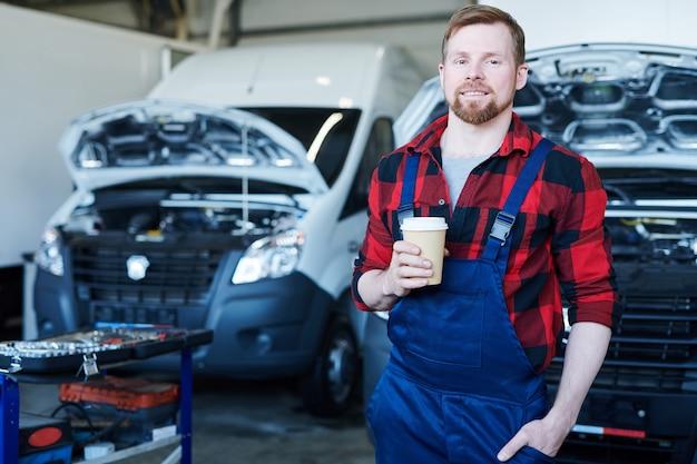 Młody mechanik lub mechanik we flaneli pije podczas przerwy w warsztacie