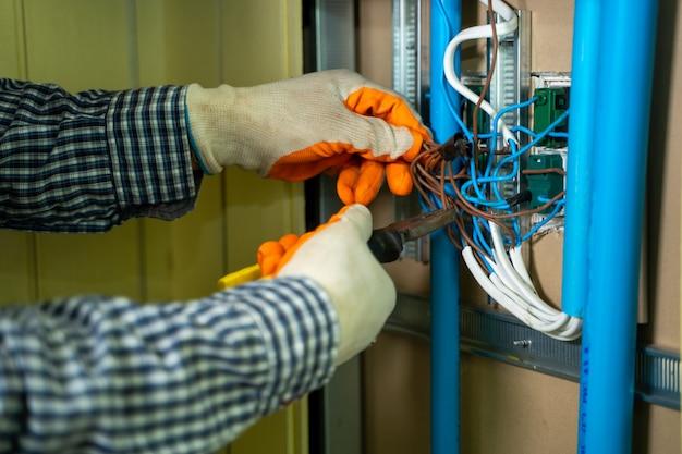 Młody mechanik mocowania elektryczne, elektryk sprawdzanie przewodów w skrzynce elektrycznej z szczypcami w korytarzu mieszkaniowej instalacji elektrycznej.