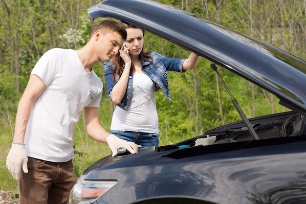 Młody mechanik patrzący na silnik samochodu