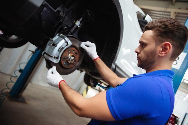 Młody mechanik samochodowy w specjalnym kombinezonie naprawia układ hamulcowy samochodu lub wymienia klocki hamulcowe