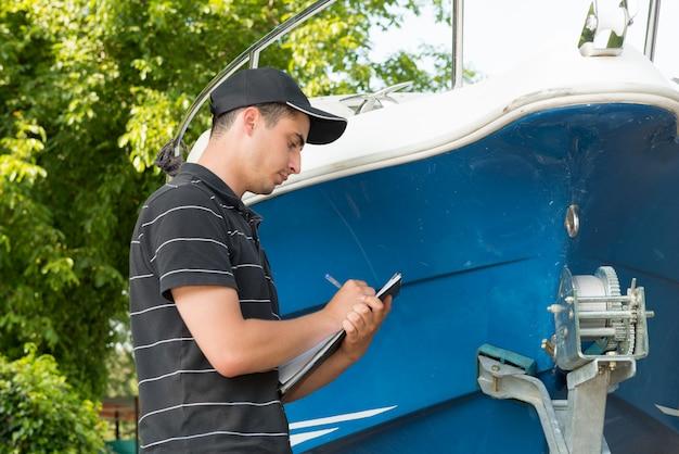 Młody mechanik sprawdza motorową łódź