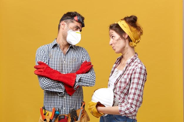 Młody mechanik stojący skrzyżowanymi rękami w masce ochronnej, koszuli i czerwonych rękawiczkach patrząc na żonę, która prosi go o odpoczynek i nie pracę, patrząc na niego z błagalnym wyrazem twarzy