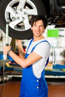 Młody mechanik w niebieskim kombinezonie pracuje nad samochodem