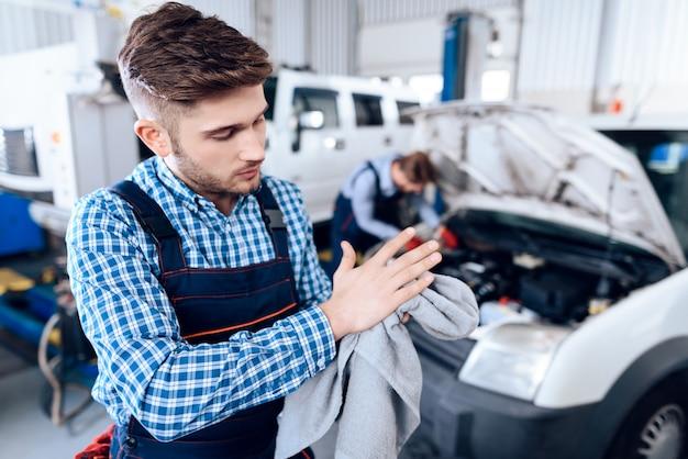 Młody mechanik wyciera ręce z ręcznikiem w garażu.