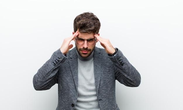 Młody menedżer człowiek zestresowany i sfrustrowany, pracujący pod presją bólu głowy i niepokojący się problemami z białą ścianą