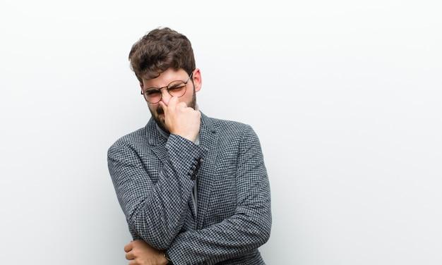 Młody menedżer czuje się zdegustowany, trzymając nos, aby uniknąć wąchania nieprzyjemnego i nieprzyjemnego smrodu na białej ścianie