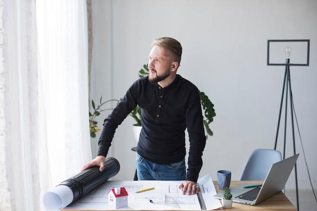 Młody męski architekt w jego biurze patrzeje daleko od