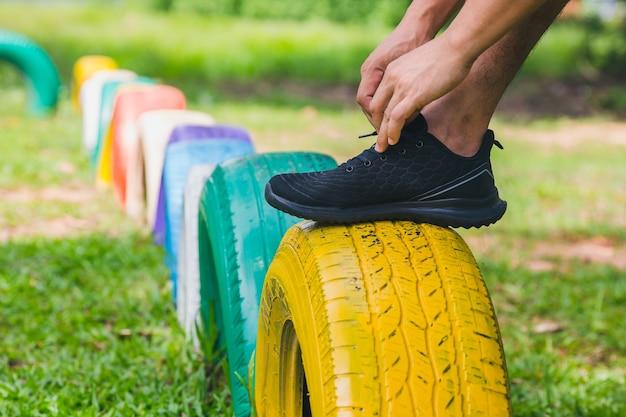Młody męski atleta wiążący jogger showlace