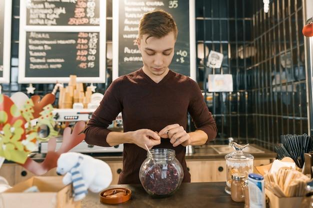 Młody męski barista przygotowywa czerwoną naturalną ziołową herbatę