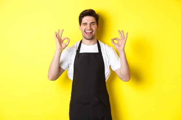 Młody męski barista w czarnym fartuchu ze znakami ok i uśmiechnięty gwarantuje jakość w kawiarni, stojąc nad żółtą ścianą