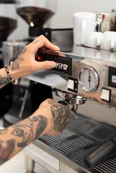 Młody męski barista z tatuażami korzystający z ekspresu do kawy w pracy
