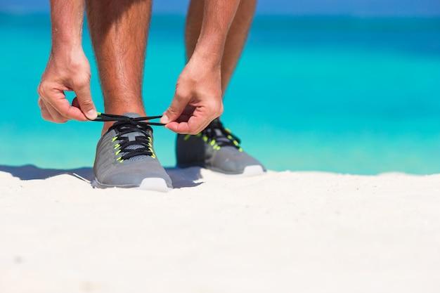 Młody męski biegacz przygotowywa zaczynać na biel plaży