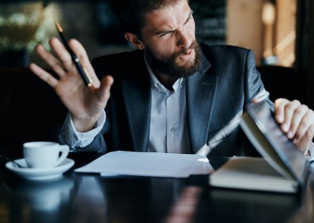 Młody męski biznesmen siedzi przy stole z papierami i pije kawę, wygląda przez okno