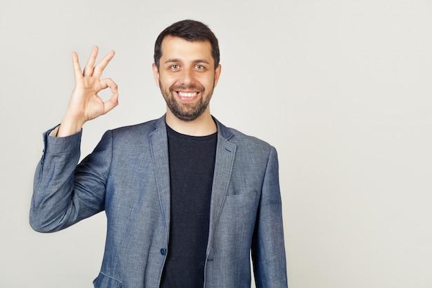 Młody męski biznesmena przedsiębiorca gwarantuje nienaganną jakość pokazuje gest potwierdzający