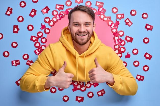 Młody męski bloger cieszy się, że ma wiele polubień i opinii, stoi wśród przycisków z znakami serca
