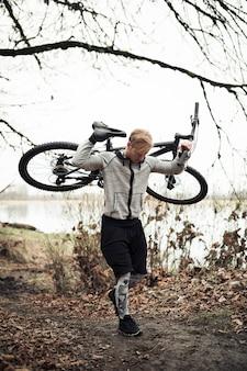 Młody męski cyklista niesie jego rowerowego odprowadzenie na śladzie