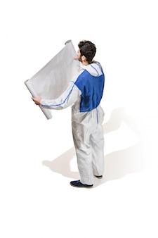 Młody męski dekorator maluje z plakatem odizolowywającym na biel ścianie.
