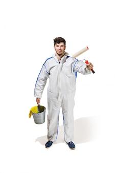 Młody męski dekoratora obraz z farba rolownikiem odizolowywającym na biel ścianie.