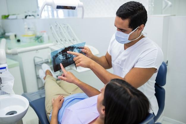 Młody męski dentysta egzamininuje promieniowanie rentgenowskie z żeńskim pacjentem