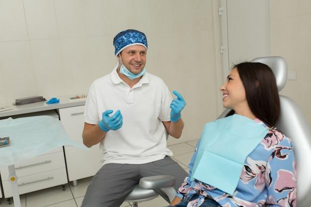 Młody męski dentysta i szczęśliwa pacjentka, scena życia w gabinecie dentystycznym, praktyka lekarska, opieka zdrowotna pacjenta