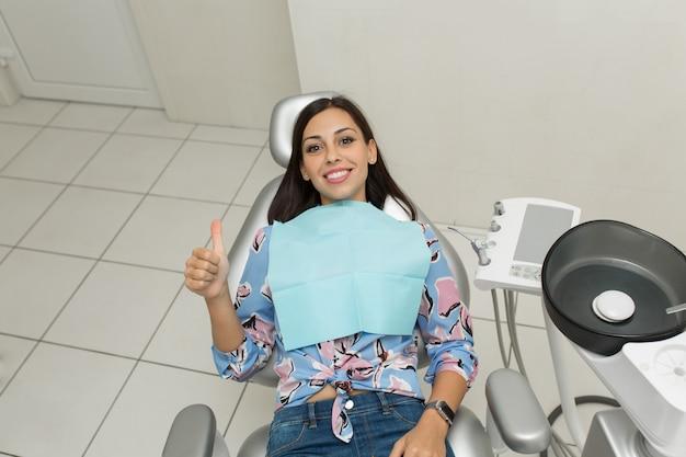 Młody męski dentysta i szczęśliwa żeńska pacjentka. scena życia biuro dentysta. praktyka lekarska. opieka zdrowotna nad pacjentem